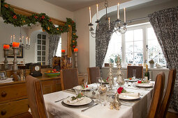 Country house dining room with Christmas garland on wall and festively set table