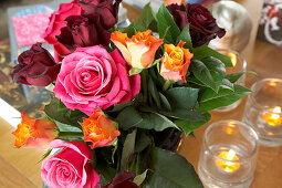 Colourful bouquet of roses and lit tealights on table