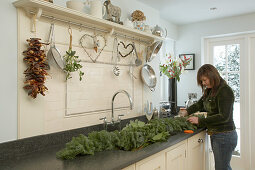 Woman tying festive garland of fir branches on dark worksurface in cream-coloured country house kitchen