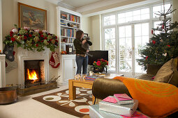 Festively decorated living room in English country house; woman holding cat in background