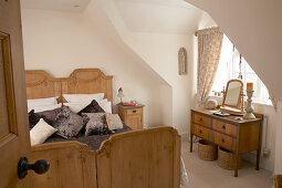 Antique twin beds and dressing table in front of dormer window in bedroom