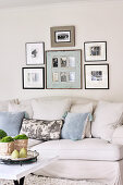 Framed black and white photographs above pale, country house sofa with scatter cushions