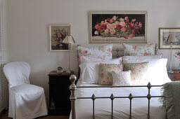 Rose-patterned cushions and pillows on metal bed with antique-inspired elements below framed painting of roses on wall