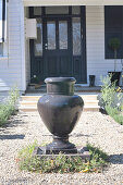 Fountain made from anthracite-coloured amphora on gravel path in front of front door