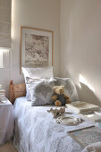 Various picture frames and teddy bear on bedspread of wooden bed