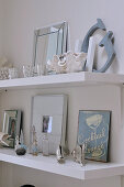 Metal sign, picture frames, shells and old perfume bottles decorating white shelves