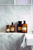 Collection of vintage bottles on shelf in bathroom with marble wall tiles