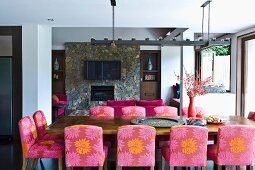 Upholstered chairs with patterned covers at dining table in front of open fireplace in stone wall