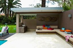 Partially roofed terrace in tropical garden with bench running along garden wall and around a corner