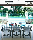 Modern table and chairs next to pool in tropical garden