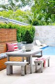 Rustic table and benches in front of pool in modern courtyard