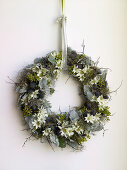 Christmas wreath with white flowers hanging on wall