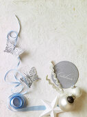 Paper butterflies next to light blue ribbon and Christmas decorations on white tablecloth with embossed pattern