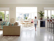 Young boy running through an open living room with a sunny dining area