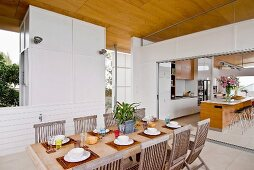Folding wooden chairs at set dining table and view of bar stools at kitchen counter through wide doorway
