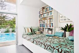 Daybed with patterned cover against bookcase on wall and next to terrace door with view of pool