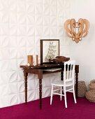 Antiker Sekretär und weisser Stuhl vor Wand mit weissen dreidimensionalen Paneelen und violetter Teppichboden
