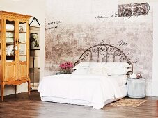 Bed with white linen and vintage metal frame against faded painting on wall and rustic, Baroque-style display cabinet