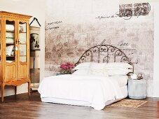 Bett mit weisser Bettwäsche und Vintage Metallgestell vor Wand mit verblasster Bemalung und Vitrinenschrank in rustikalem Barockstil