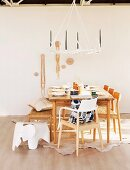 Stools and chairs at set dining table below chandelier made from antlers