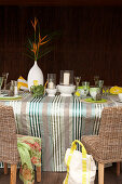 Decorated table with candles and glass candle covers on a striped table cloth in front of a dark wood wall