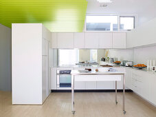 Table on castors in open-plan white kitchen