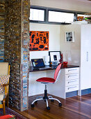 A quiet work area in a niche next to a built-in cupboard and a stone wall