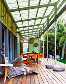 A glass-roofed veranda with comfortable wicker loungers and a large wooden dining table with orange plastic chairs