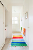 Bright, striped runner on floor of white corridor