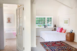 View into simple bedroom with colourful rug
