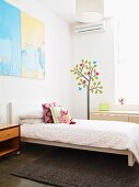 Bright, spartan child's bedroom with cheerful mural next to window