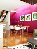 Pleasant dining area with purple wall, long dining table with metal legs and white designer chairs