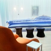 Eclectic mix of styles in Postmodern London hotel lounge - rustic wooden stools in front of delicate, extra-long sofa covered in sky-blue satin and plain, apricot armchair next to functional metal table