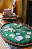 Antique finds on baize-covered tray next to stack of books on fender seat