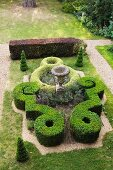 Garden design in style of castle grounds with antique amphora amongst artistic topiary box hedges