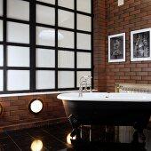 Vintage-style bathroom with free-standing bathtub against brick-effect wall