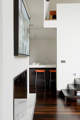 View of kitchen counter and bar stools from designer living room