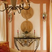 China bowl and candelabras on French console table below relief portraits