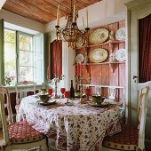 French country house style in dining room with rustic shelving and antique chandelier