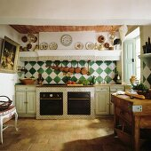 Traditional, French-style country house kitchen with stone floor and chequered wall tiles