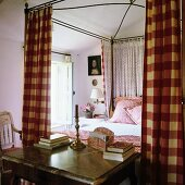 French canopy bed with red and white gingham and spotted curtains