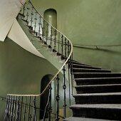 Vintage Treppenhaus - Schmiedeeisernes Metallgeländer an wendelnder Treppe und grün grau getönte Wände mit kleinen Nischen