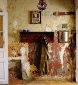 Offene Garderobe aus Holz mit aufgehängtem Mantel an Wand mit abblätternder Farbe in schlichtem Hausflur