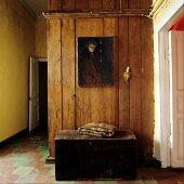 Alte Truhe vor Holzwand mit Gemälde in schlichtem Hausflur