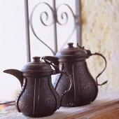 Dark, metal Moroccan teapots on windowsill