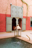 Lantern on edge of pool in Moroccan courtyard with arched entrances in red-painted wall
