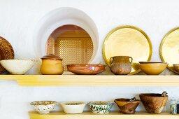 Ethnic earthenware pots on simple wall-mounted shelves