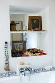 Mediterranean ambiance in bathroom with necklaces on shelf in niche above bathtub