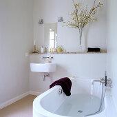 A half-filled bath tub in a minimalist bathroom