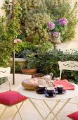 Breakfast on a bistro table with white metal chairs and plant pots on the terrace